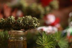 Huilez le cannabis dans une bouteille et le chanvre sur un fond de Noël photographie stock