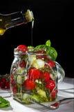 Huilez le versement dans un pot de maçon avec les légumes frais sur le backgro foncé Photographie stock libre de droits