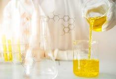 Huilez le versement, formulant le produit chimique pour la médecine, recherche de laboratoire, laissant tomber le liquide au tube Photo stock