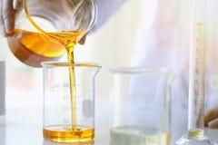 Huilez le versement, l'équipement et les expériences de la science, formulant le produit chimique pour la médecine images stock