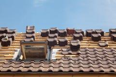 Huis in aanbouw Dakwerktegels met open dakraam stock foto