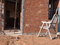 Huis in aanbouw met witte stoel royalty-vrije stock foto