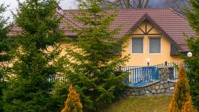 Huis achter mooie pijnboombomen royalty-vrije stock afbeelding