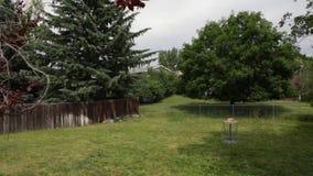Huis achtertuin met bomen en het doel van het schijfgolf stock footage