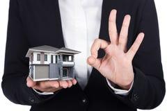 Huis in bedrijfs menselijke hand en O.K. die teken op wit wordt geïsoleerd Royalty-vrije Stock Afbeelding