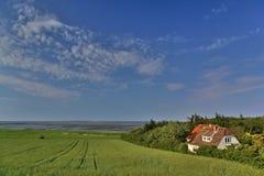 Huis bij de kust met gebied en getijdemudflats stock afbeelding