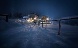 Huis coverd met sneeuw bij nacht stock afbeelding