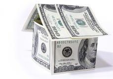 Huis dat van dollars op witte achtergrond wordt gemaakt Stock Foto
