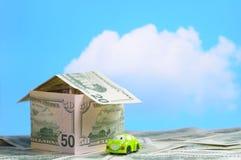 Huis dat van geld en een stuk speelgoed auto wordt gebouwd Royalty-vrije Stock Afbeeldingen