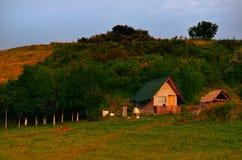 Huis in de wildernis op zonsondergang Stock Afbeeldingen