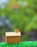 Huis die van oud kringloopdocument vakje maken die op groen grasgebied liggen Stock Afbeeldingen