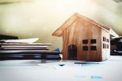Huis en bezit voor verkoopconcept, houten huisstuk speelgoed op bureau DE stock foto's