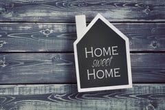 Huis gevormd bord op houten achtergrond Royalty-vrije Stock Foto's