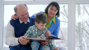 Huis het scholen, jong geitje met grootmoeder en grootvader gelezen sprookjes stock footage