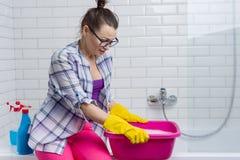 Huis het schoonmaken De vrouw maakt thuis in de badkamers schoon stock fotografie