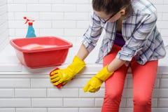 Huis het schoonmaken Vrouw de badkamers schoonmaken, wijfje in vrijetijdskleding met detergens en washandje die thuis in de badka royalty-vrije stock foto