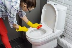 Huis het schoonmaken Vrouwen schoonmakend toilet, wijfje in vrijetijdskleding met detergens en washandje thuis in de badkamers royalty-vrije stock afbeelding