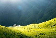 Huis in het zonlicht, in een groene bergvallei Stock Foto's