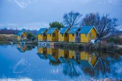 Huis in meer dichtbij berg wordt weerspiegeld die Stock Afbeelding