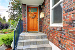 Huis met baksteenversiering Ingangsportiek met oranje deur Royalty-vrije Stock Fotografie