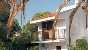 Huis met balkon onder groene bomen stock video