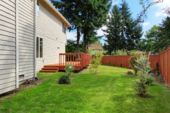 Huis met bruin stakingsdek en houten omheining Stock Fotografie