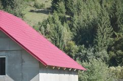 Huis met een dak van stevige die metaalbladen wordt, als een oude tegel worden gevormd gemaakt die royalty-vrije stock afbeelding