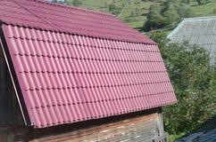 Huis met een dak van stevige die metaalbladen wordt, als een oude tegel worden gevormd gemaakt die stock afbeeldingen