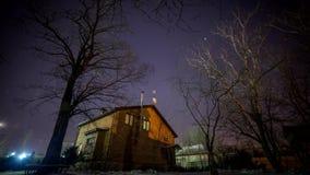 Huis met een venster Dynamisch licht Omwenteling van de sterren en de Melkweg naast het huis Glans op de pijnbomen van de brand stock videobeelden