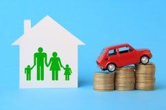 Huis met familiesymbool, miniatuurauto en muntstukken Stock Fotografie