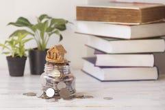 Huis met muntstukken, installatie en boekachtergrond op lijst Royalty-vrije Stock Afbeeldingen
