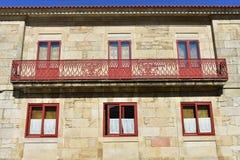 Huis met rode ijzerleuning, steenmuren en rode houten vensters Pontevedra, Galicië, Spanje Zonnige dag, blauwe hemel stock foto's