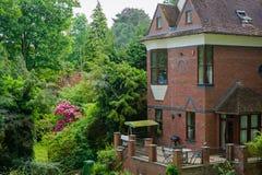 Huis met terras en groene tuin stock foto