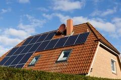 Huis met zonnepanelen en blauwe hemel Stock Fotografie
