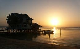 Huis met zonsondergang op de kust Royalty-vrije Stock Afbeelding