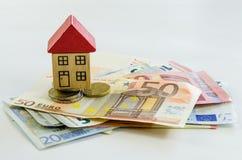 Huis, muntstukken en bankbiljetten Stock Afbeeldingen