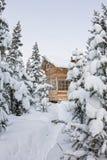 Huis onder sneeuw in de winter houten chalet onder nette bomen in royalty-vrije stock afbeeldingen