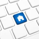 Huis of onroerende goederenconcept, blauwe huisknoop of sleutel op een toetsenbord Stock Foto's