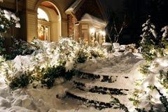 Huis op de sneeuwlichten van nachtKerstmis stock foto's