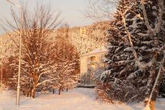Huis op de zonsondergang, met snow-covered bos op achtergrond Th Stock Afbeelding