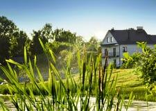 Huis op een rivieroever Stock Fotografie
