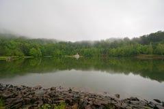 Huis op meer en wolken Stock Afbeelding