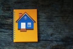 Huis op oranje notitieboekje op uitstekende houten achtergrond Royalty-vrije Stock Foto's