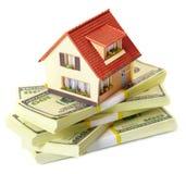 Huis op pakken bankbiljetten Stock Afbeeldingen
