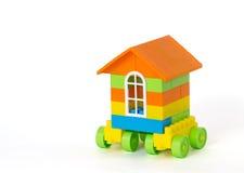 Huis op wielen van plastic bakstenen worden gemaakt die Geïsoleerdj op witte achtergrond Stock Foto's