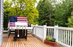 Huis openluchtterras met BBQ kooktoestel die voor vakantiepicknick voorbereidingen treffen Royalty-vrije Stock Foto