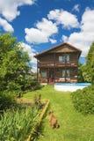 Huis, pool en rode hond op een groen gazon Stock Fotografie