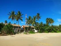 Huis tussen palmen bij het strand Stock Afbeelding