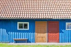 Huis van blauwe houten planken, rood dak, twee kleurrijke deuren en kleine vensters Royalty-vrije Stock Foto
