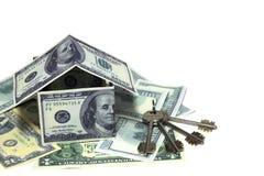 Huis van dollarrekeningen wordt gemaakt met sleutel die stock foto's